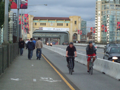 Pedestrians on the sidewalk and cyclists in their own lane on the southbound side